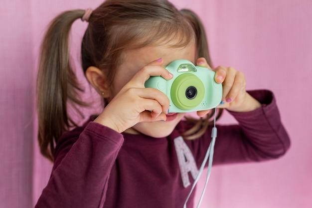 Porträt kleines mädchen, das mit kamera spielt