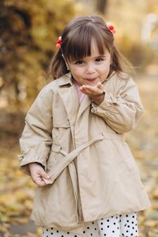 Porträt kleines mädchen in einem beigen mantel geht in den herbstpark