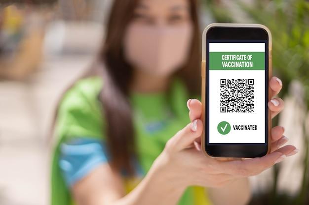Porträt lächelnde frau posiert mit impfausweis auf smartphone-bildschirm coronavirus-prävention