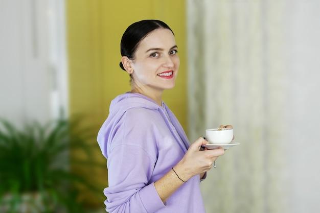 Porträt lächelnde junge frau in der freizeitkleidung, die allein steht und weiße kaffeetasse hält