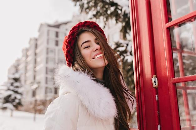 Porträt lächelnde winterfrau mit langen brünetten haaren in der roten strickmütze, die auf straße nahe roter telefonzelle kühlt. schnee, kaltes wetter, sonniger morgen, strahlende gefühle, glück.