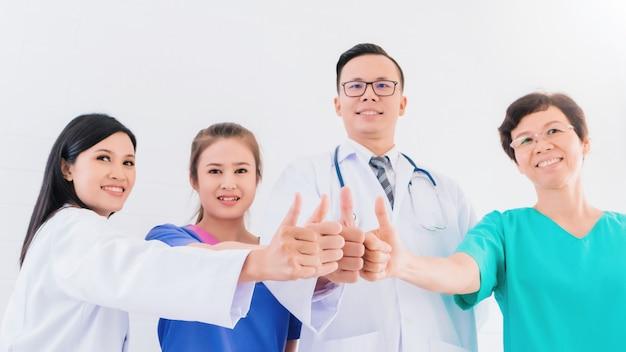 Porträt lächelnden asiatischen medizinischen männlichen doktors, der sich handdaumen mit teampersonal im krankenhaus steht und zeigt.