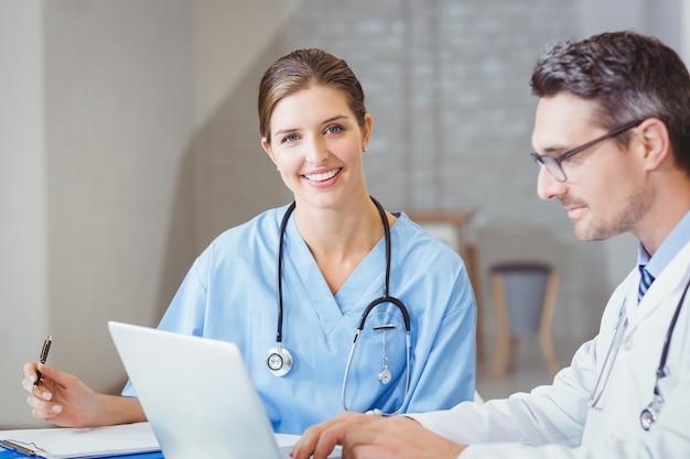 Porträt lächelnden doktors sitzend am schreibtisch mit kollegen