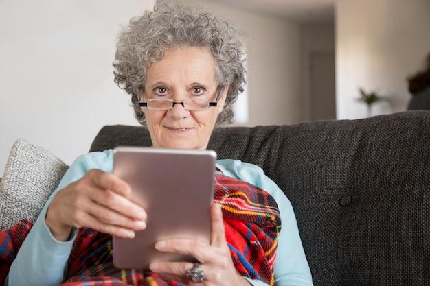 Porträt lächelnder alter dame, die digitale tablette im wohnzimmer verwendet