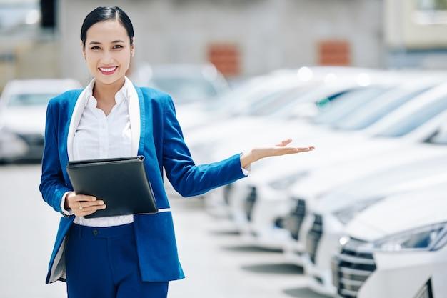 Porträt lächelnder junger weiblicher asiatischer autohausmanager mit lederordner, der junge einlädt, ein auto zu wählen