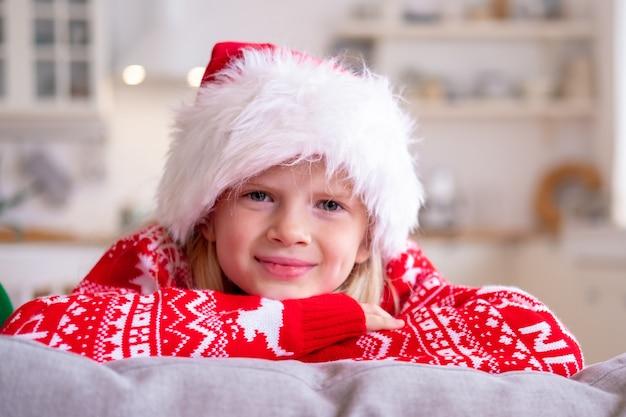 Porträt lächelndes mädchen in der weihnachtsmütze und im weihnachtskostüm zu hause