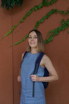 Porträt lässige frau mit schönem weißen lächeln, im blauen kleid, mit rucksack über brauner wand mit grünen blättern darauf