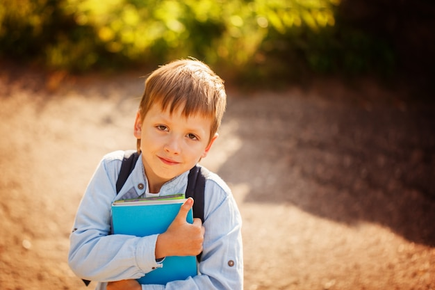 Porträt littleschoolboy mit rucksack und büchern. draußen