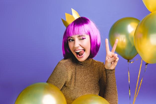 Porträt lustige junge frau mit lila haarschnitt spaß haben. goldene luftballons umgeben, zeigen zunge, drücken positive gesichtsgefühle aus, krone auf kopf, geburtstagsfeier.