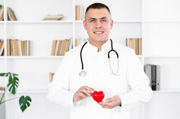 Porträt männlichen doktors ein plüschherz halten