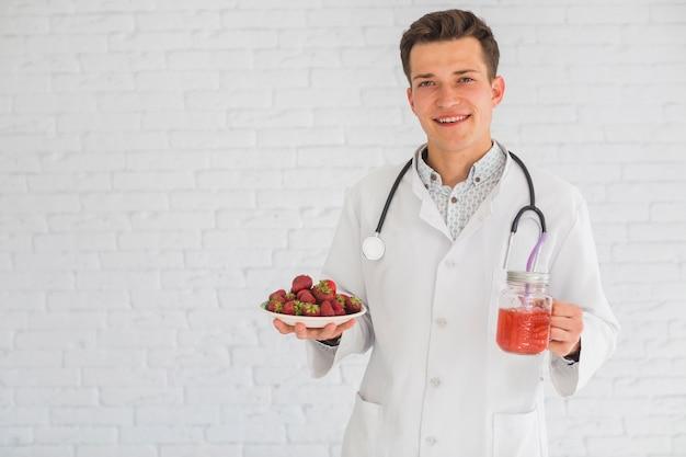 Porträt männlichen doktors erdbeerefrüchte und smoothie halten