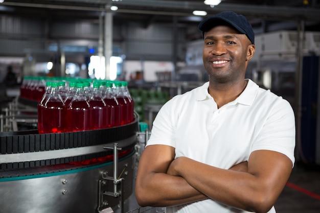 Porträt männlicher arbeiter, der in der kaltgetränkefabrik steht