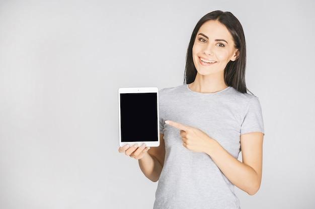 Porträt mit kopienplatz leeren platz der frau in lässig mit tablette in händen, die kamera lokalisiert auf weißem hintergrund betrachten.