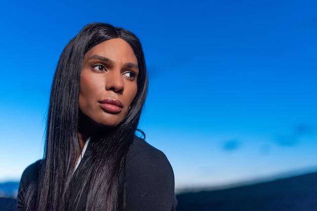 Porträt mit kopienraum einer transgender-frau, die bei sonnenuntergang mit abgelenktem ausdruck beiseite schaut