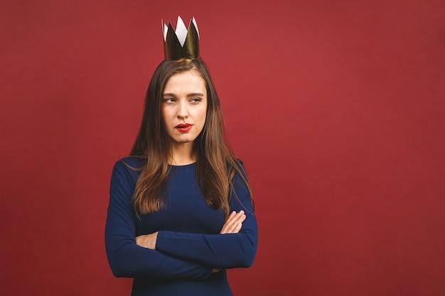 Porträt mit kopyspace leerem platz der selbstbewussten stolzen arroganten jungen frau mit goldener krone auf ihrem kopf lokalisiert auf rotem hintergrund.