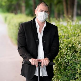 Porträt mit medizinischer maske, die roller reitet