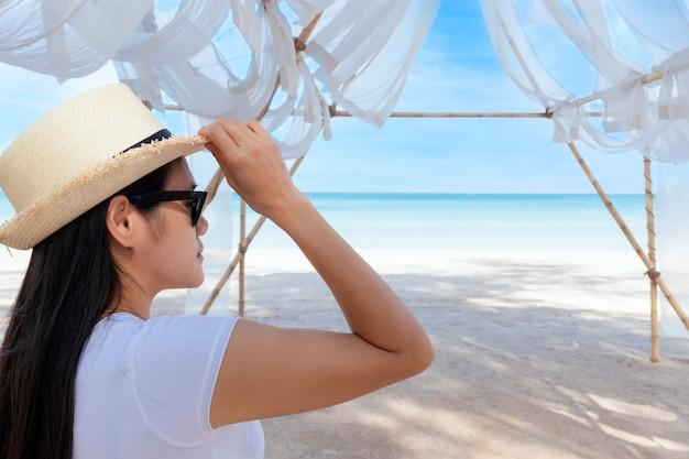 Porträt-mittelschussansicht der frau stehen im weißen t-shirt und im hut, die in richtung blauen ozean und himmel schauen