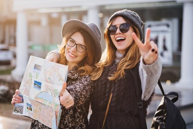 Porträt modische lächelnde frauen, die helle gefühle am sonnigen tag in der stadt ausdrücken. viel spaß beim gemeinsamen reisen, schöne momente mit fröhlichen touristen, stilvollem aussehen, urlaub genießen, glück.