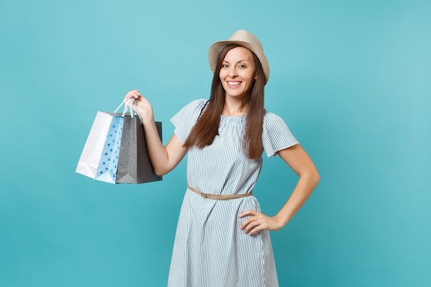 Porträt modische lächelnde schöne kaukasische frau im sommerkleid, strohhut, der pakete mit einkäufen nach dem einkaufen auf blauem pastellhintergrund hält. kopieren sie platz für werbung.