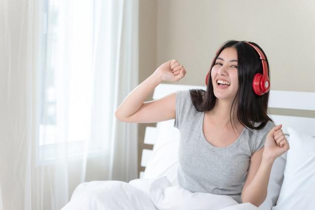 Porträt nah herauf die hübsche jugendfrau, die roten bluetooth kopfhörer trägt