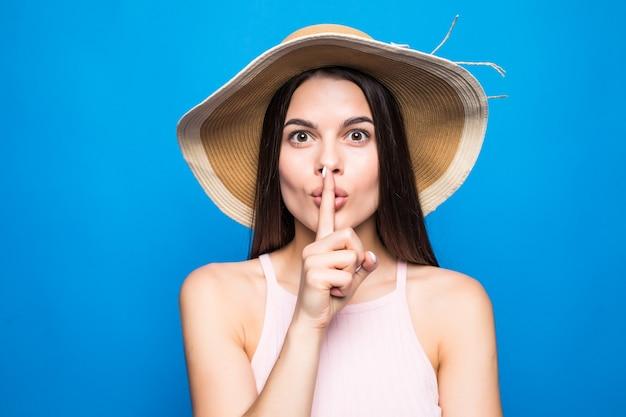 Porträt-nahaufnahme der frau, die strohhut zeigt finger an den lippen, um geheimnis über blaue wand isoliert zu halten.