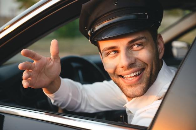 Porträt-nahaufnahme des jungen kaukasischen chauffeurmannes, der uniform und mütze trägt, lächelnd und gruß vom autoseitenfenster