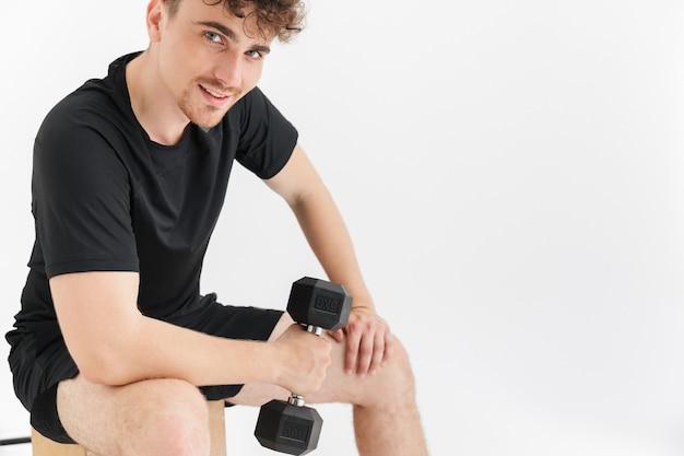 Porträt-nahaufnahme eines attraktiven sportlichen mannes im t-shirt, der auf einem stuhl sitzt und während des trainings hanteln hebt, isoliert über weißer wand