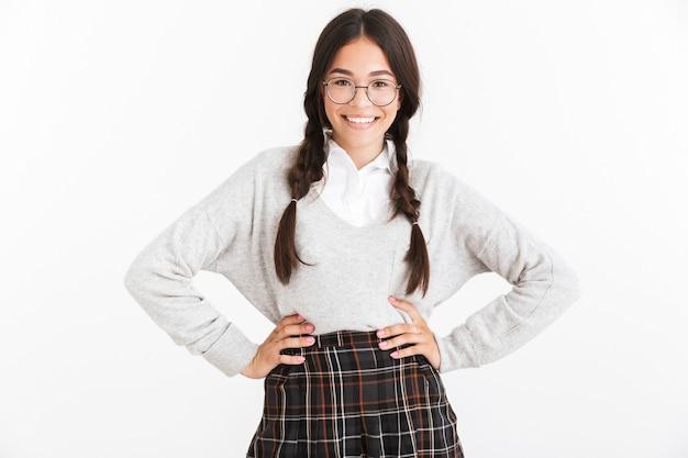 Porträt nahaufnahme eines kaukasischen teenager-mädchens mit brille und schuluniform, das in die kamera lächelt, die über weiße wand isoliert ist?