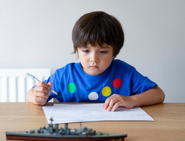 Porträt netter kleiner schuljunge, der schlachtschiff zeichnet, kind, das mit modellschiffspielzeug spielt und auf papier skizziert, indoors actvitiy konzept