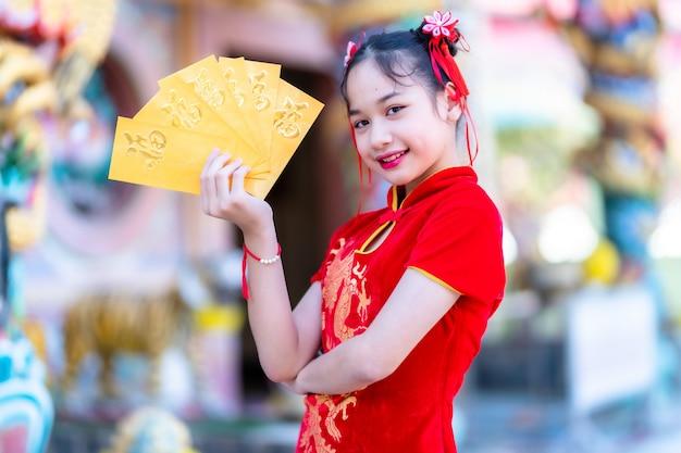 Porträt nettes kleines asiatisches mädchen, das rotes traditionelles chinesisches cheongsam trägt, gelbe umschläge mit dem chinesischen text segen auf ihnen geschrieben hält