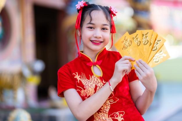 Porträt nettes kleines asiatisches mädchen, das rotes traditionelles chinesisches cheongsam trägt und gelbe umschläge mit dem chinesischen text hält