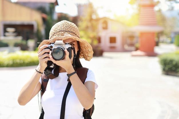 Porträt niedliche asiatische fotografin frau bedecken ihr gesicht mit kamera. attraktive schöne reisende asiatische frauen im weißen hemd und im hut mit rucksack, die spaß in der sommerzeit der stadt asien im freien haben.