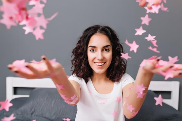 Porträt niedliche fröhliche hübsche junge frau im pyjama mit lockigem brünettem haar, das spaß auf bett hat. stretching hände mit rosa lametta, expressinf glück