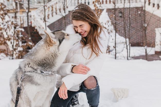 Porträt niedliche schöne momente des husky-hundes, der modische junge frau im freien im schnee küsst. fröhliche stimmung, winterferien, schneezeit, echte freundschaft, tierliebe.