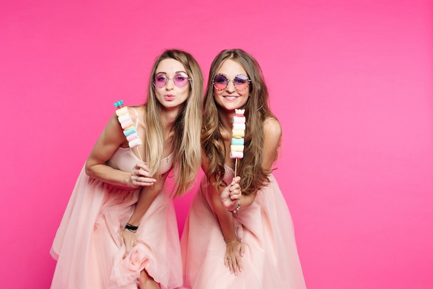 Porträt o zwei und süße mädchen, in rosa sonnenbrille und sieht aus wie prinzen oder süßigkeiten, kuss in die kamera senden. frauen zeigen marshmallows am stock und haben spaß. mode.