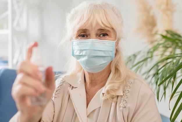 Porträt oma mit maske und desinfektionsmittel