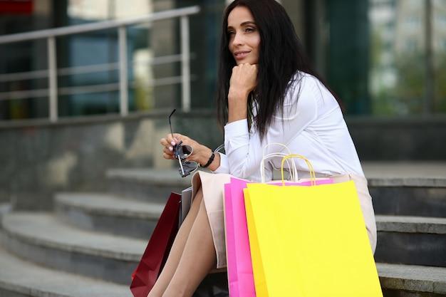 Porträt perfekter dame in der stilvollen kleidung, die moderne sonnenbrille hält. einkaufs- und modekonzept.