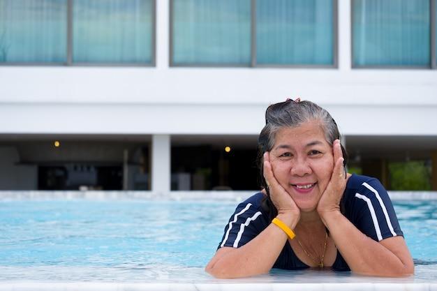 Porträt reifer frau asiens, die in einem swimmingpool an hand setzt ihr kinn und schaut vorwärts steht