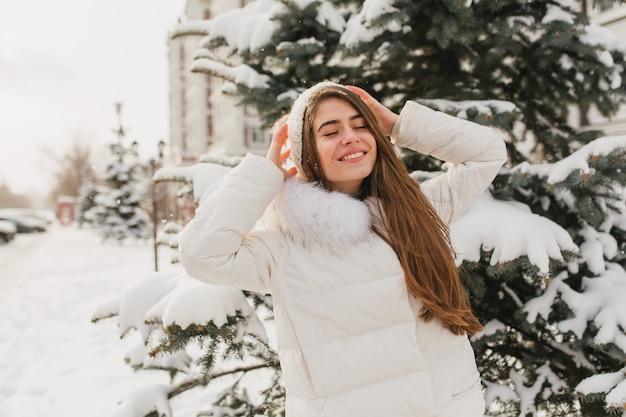 Porträt reizende niedliche frau, die auf sonnenschein im gefrorenen morgen kühlt. junge freudige frau, die winterzeit auf tannenbäumen voll mit schnee genießt. positive wahre gefühle, lächelnd mit geschlossenen augen.
