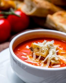 Porträt schießende tomatensuppe mit crackern und käsetomaten und brot auf dem tisch