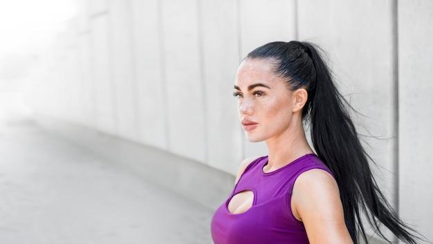 Porträt schön von einer sportlichen jungen frau draußen. eignungsfrau beim stilvollen kleidungstrainieren.