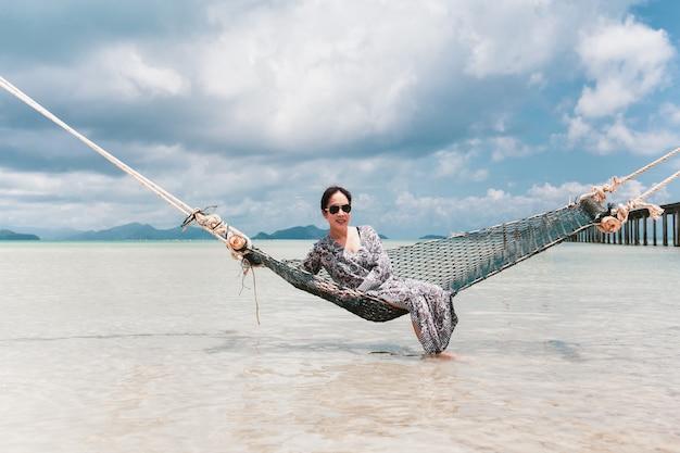 Porträt schöne asiatische frau, die auf hängematte im meer im urlaub sitzt.