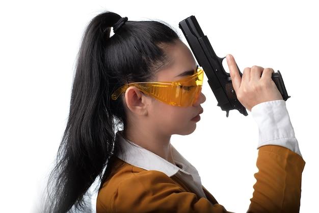 Porträt schöne asiatische frau, die einen gelben anzug eine hand hält, die eine pistolenpistole hält
