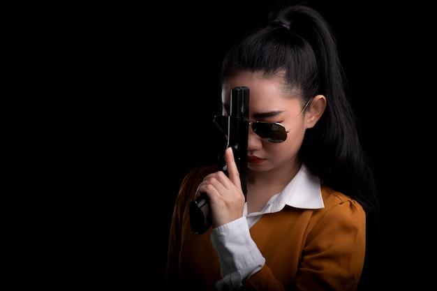 Porträt schöne asiatische frau, die einen gelben anzug eine hand hält pistolenpistole am schwarzen hintergrund trägt
