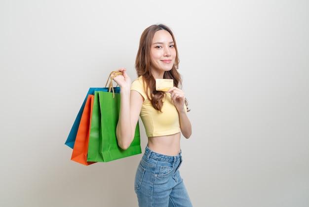 Porträt schöne asiatische frau mit einkaufstasche und kreditkarte auf weißem hintergrund