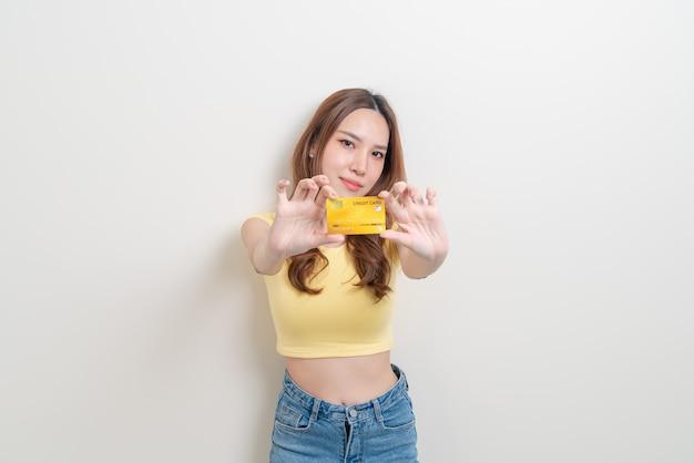 Porträt schöne asiatische frau mit kreditkarte auf weißem hintergrund