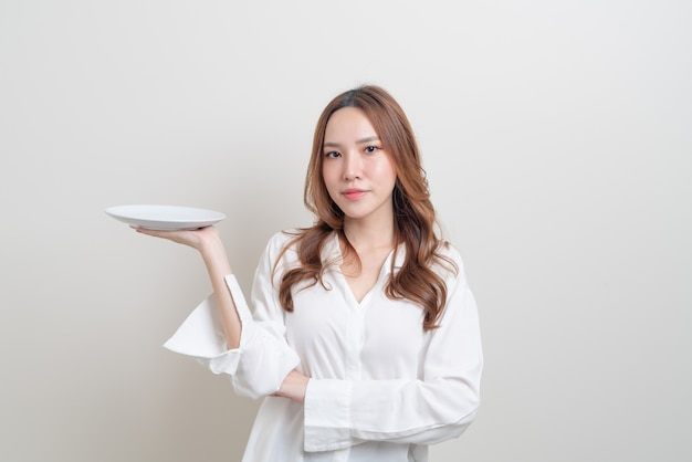 Porträt schöne asiatische frau mit leeren teller auf weißem hintergrund