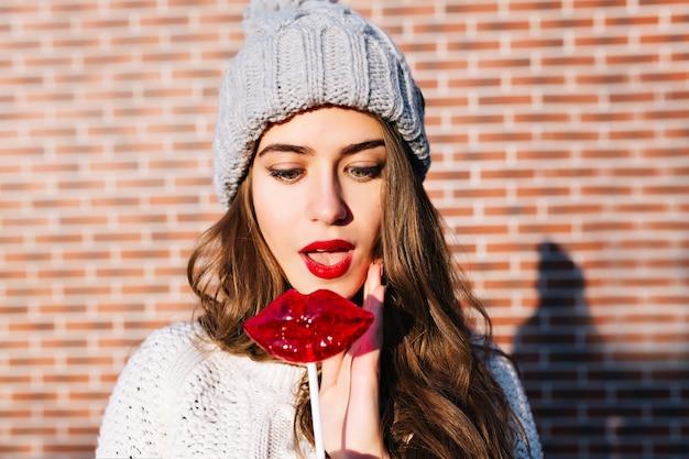 Porträt schöne brünette mädchen mit langen haaren in strickmütze an der wand außerhalb. sie sieht erstaunt auf die roten lippen der lutscher aus.