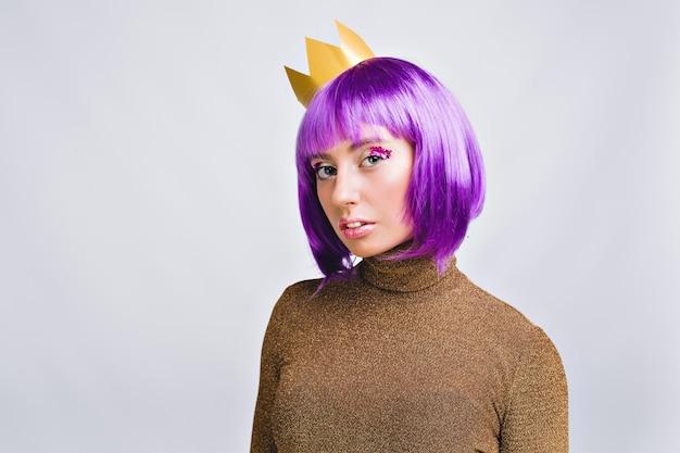 Porträt schöne frau mit lila haarschnitt in goldkrone. sie hat ein strahlendes make-up und sieht aus