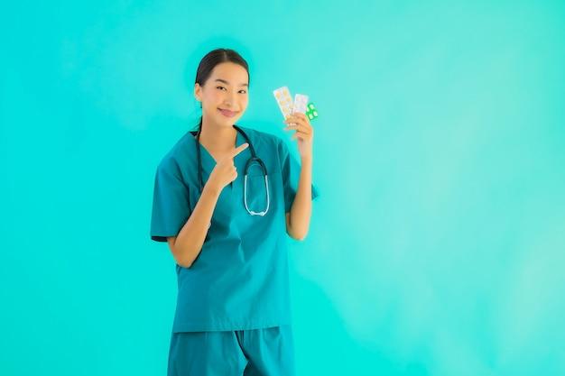 Porträt schöne junge asiatische ärztin mit pille oder droge und medizin